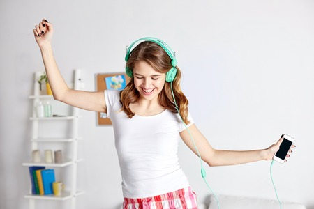 Photo for people, leisure and technology concept - happy woman or teenage girl in headphones listening to music from smartphone and dancing on bed at home - Royalty Free Image