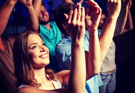 Photo for party, holidays, celebration, nightlife and people concept - smiling friends applauding at concert in club - Royalty Free Image