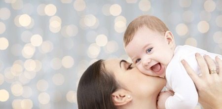 Photo pour family, motherhood, children, parenthood and people concept - happy mother kissing her baby over holidays lights background - image libre de droit