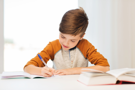 Foto de education, childhood, people, homework and school concept - smiling student boy with book writing to notebook at home - Imagen libre de derechos