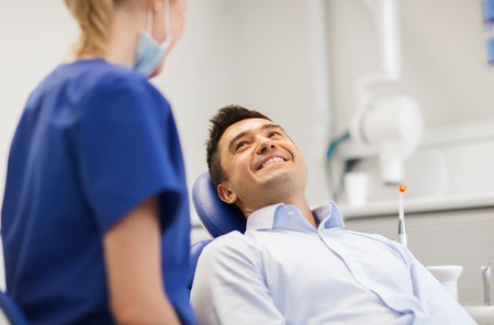 Foto de people, medicine, stomatology and health care concept - female dentist talking to happy male patient at dental clinic office - Imagen libre de derechos