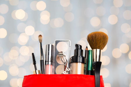 Photo pour cosmetics, makeup, holidays and beauty concept - close up of cosmetic bag with makeup stuff over lights background - image libre de droit