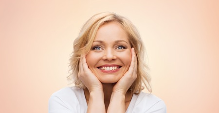 Photo for beauty, people and skincare concept - smiling middle aged woman in white shirt touching face over beige background - Royalty Free Image
