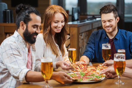 Photo pour leisure, food and drinks, people and holidays concept - smiling friends eating pizza and drinking beer at restaurant or pub - image libre de droit