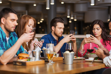 Photo pour leisure, technology, lifestyle and people concept - friends with smartphones dining at restaurant - image libre de droit