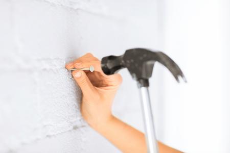 Foto de architecture and home renovation concept - architect hammering nail in wall - Imagen libre de derechos