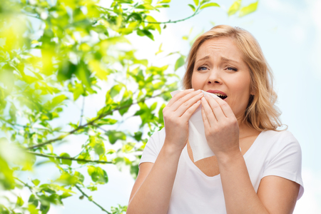 Foto de people, healthcare, rhinitis and allergy concept - unhappy woman with paper napkin sneezing over green natural background - Imagen libre de derechos