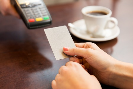 Photo pour people, finance, technology and consumerism concept - close up of waitress holding credit card reader and customer hand entering pin code at cafe - image libre de droit