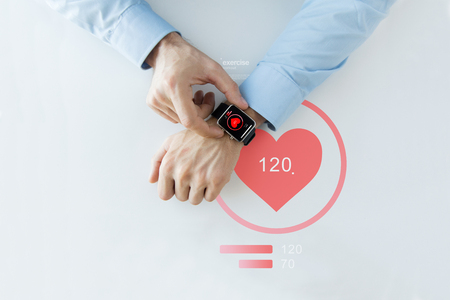 Foto de business, technology, health care, application and people concept - close up of male hands setting smart watch with red heart icon screen - Imagen libre de derechos