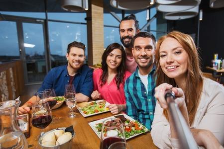 Foto de leisure, technology, friendship, people and holidays concept - happy friends having dinner and taking picture by selfie stick at restaurant - Imagen libre de derechos
