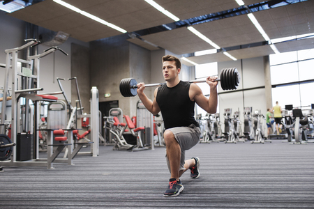 Foto de sport, bodybuilding, lifestyle and people concept - young man with barbell flexing muscles and making shoulder press lunge in gym - Imagen libre de derechos