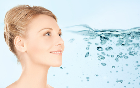 beauty, people, moisturizing, body care and health concept - smiling young woman face over water splash background