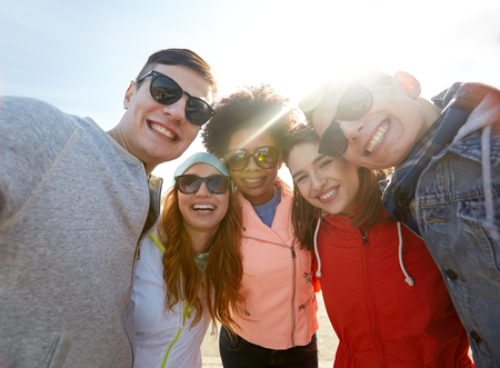 Photo pour tourism, travel, people, leisure and technology concept - group of smiling teenage friends taking selfie outdoors - image libre de droit