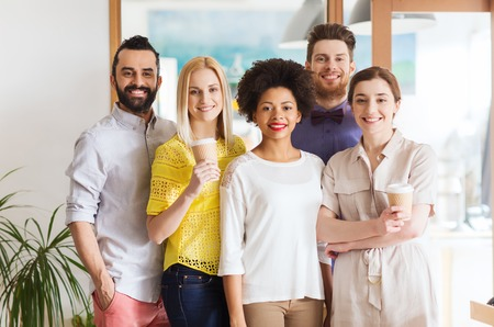 Foto de business, startup, people, drinks and teamwork concept - happy smiling international creative team with disposable paper coffee cups in office - Imagen libre de derechos
