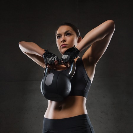 Photo for fitness, sport, exercising, weightlifting and people concept - young woman flexing muscles with kettlebell in gym - Royalty Free Image