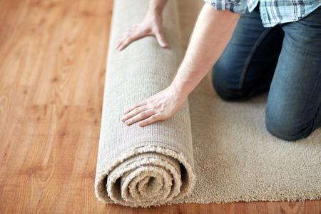 Photo pour repair, building and home concept - close up of male hands rolling carpet - image libre de droit