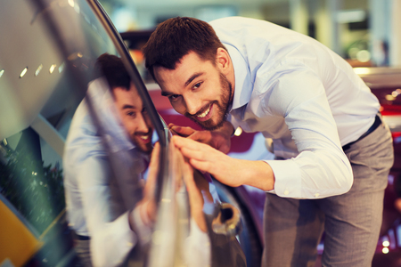 Photo pour auto business, car sale, consumerism and people concept - happy man touching car in auto show or salon - image libre de droit