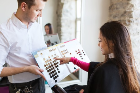 Foto de beauty, hair dyeing and people concept - happy young woman with hairdresser choosing hair color from palette samples at salon - Imagen libre de derechos