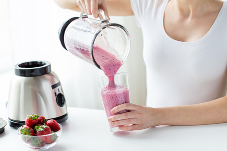 Photo for healthy eating, cooking, vegetarian food, dieting and people concept - close up of woman with blender and strawberries pouring milk shake to glass at home - Royalty Free Image