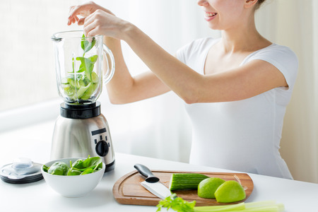 Photo for healthy eating, cooking, vegetarian food, dieting and people concept - close up of young woman with blender and green vegetables making detox shake or smoothie at home - Royalty Free Image