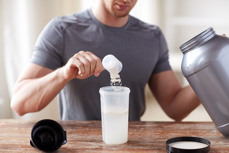 Photo for sport, fitness, healthy lifestyle and people concept - close up of man with jar and bottle preparing protein shake - Royalty Free Image