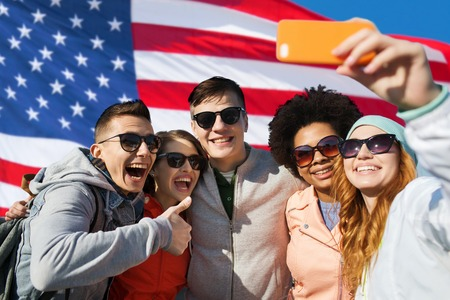 Photo pour people, international friendship and technology concept - group of happy teenage friends taking selfie with smartphone and showing thumbs up over american flag background - image libre de droit