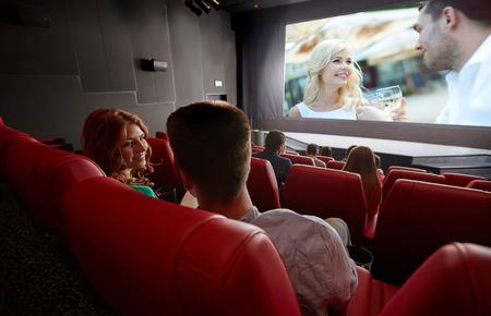 Photo pour cinema, entertainment, communication and people concept - happy couple of friends watching movie and talking in theater from back - image libre de droit