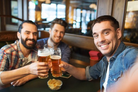 Foto de people, leisure, friendship, technology and bachelor party concept - happy male friends taking selfie and drinking beer at bar or pub - Imagen libre de derechos