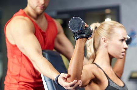 Foto de sport, fitness, bodybuilding, lifestyle and people concept - man and woman with dumbbells flexing muscles in gym - Imagen libre de derechos