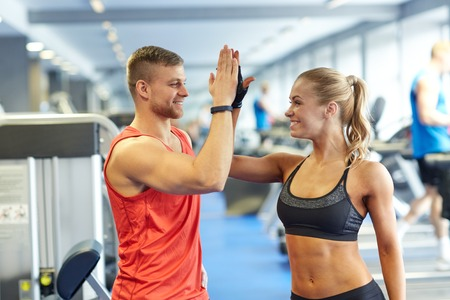 Photo pour sport, fitness, lifestyle, gesture and people concept - smiling man and woman doing high five in gym - image libre de droit