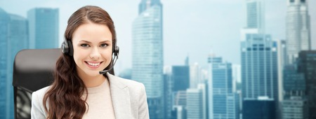 Foto de people, online service, communication and technology concept - smiling female helpline operator with headset over singapore city background - Imagen libre de derechos