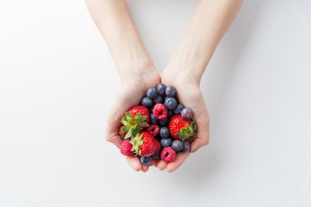Photo for healthy eating, dieting, vegetarian food and people concept - close up of woman hands holding berries at home - Royalty Free Image