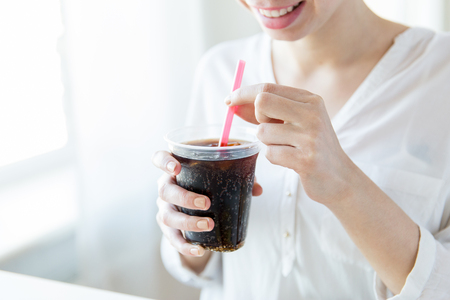 Foto de drinks, people and lifestyle concept - close up of happy woman drinking coca cola from plastic cup with straw at home - Imagen libre de derechos