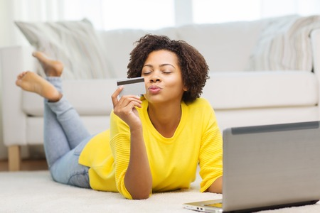 Photo pour people, internet bank, online shopping, technology and e-money concept - happy african american young woman lying on floor with laptop computer and credit card at home - image libre de droit