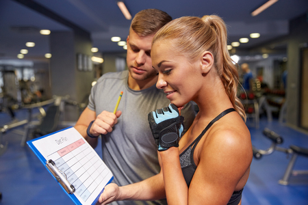 Foto de fitness, sport, exercising and diet concept - smiling young woman with personal trainer and exercise plan on clipboard in gym - Imagen libre de derechos