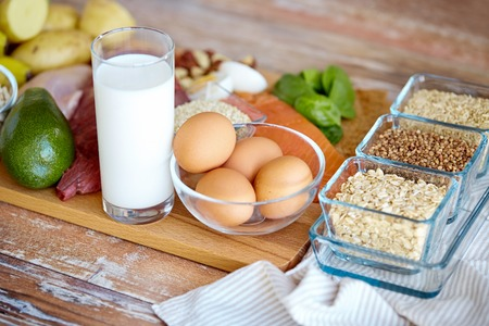 Foto de balanced diet, cooking, culinary and food concept - close up of eggs, cereals and milk glass on wooden table - Imagen libre de derechos
