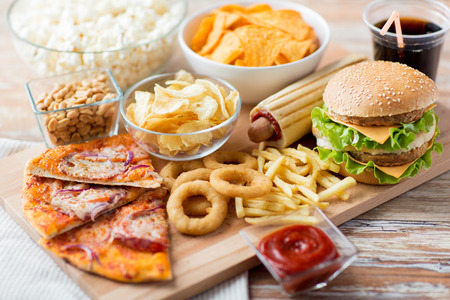 fast food and unhealthy eating concept - close up of fast food snacks and cola drink on wooden table