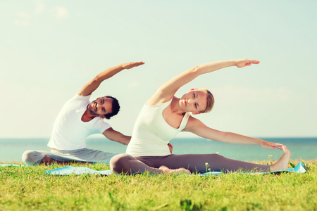 Photo pour fitness, sport, friendship and lifestyle concept - smiling couple making yoga exercises sitting on mats outdoors - image libre de droit