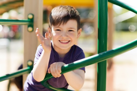 Photo pour summer, childhood, leisure, gesture and people concept - happy little boy waving hand on children playground climbing frame - image libre de droit