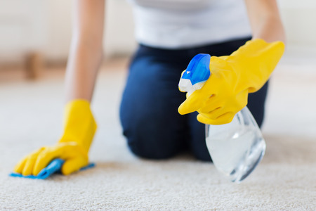 Foto de people, housework and housekeeping concept - close up of woman in rubber gloves with cloth and detergent spray cleaning carpet at home - Imagen libre de derechos