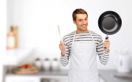 Foto de people, cooking and culinary concept - happy man or cook in apron with frying pan and wooden spoon over home kitchen background - Imagen libre de derechos