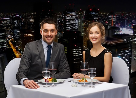 Photo for restaurant, couple and holiday concept - smiling couple eating main course with red wine at restaurant - Royalty Free Image