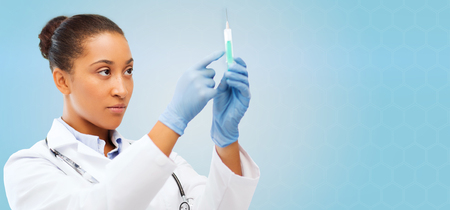 Foto de healthcare, vaccination, anesthesia and medical concept - african american female doctor holding syringe with injection over blue background - Imagen libre de derechos