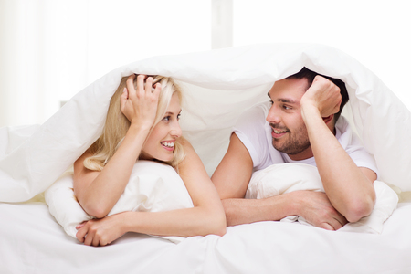 Foto de people, family, bedtime and happiness concept - happy couple lying in bed covered with blanket over head and talking at home - Imagen libre de derechos