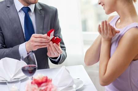 couple, love, engagement and holiday concept - close up of excited young woman and boyfriend giving her ring at restaurant