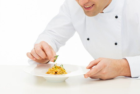 Foto de cooking, profession, haute cuisine, food and people concept - close up of happy male chef cook decorating dish - Imagen libre de derechos