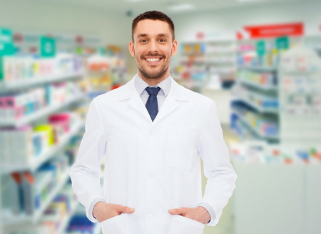 Photo for medicine, pharmacy, people, health care and pharmacology concept - smiling male pharmacist in white coat over drugstore background - Royalty Free Image