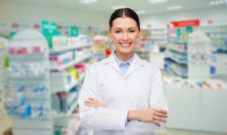 Foto de medicine, pharmacy, people, health care and pharmacology concept - happy young woman pharmacist over drugstore background - Imagen libre de derechos