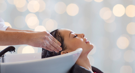 Photo pour beauty salon, hair care and people concept - hairdresser hands washing happy young woman head over holidays lights background - image libre de droit