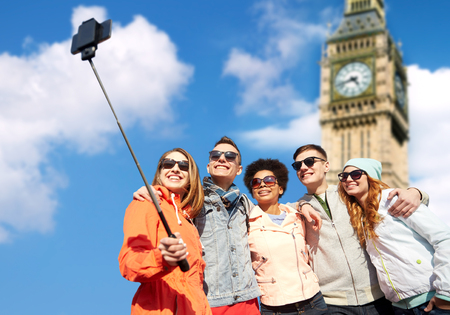 Photo for tourism, travel, people, leisure and technology concept - group of smiling teenage friends taking selfie with smartphone and monopod over london big ben tower background - Royalty Free Image